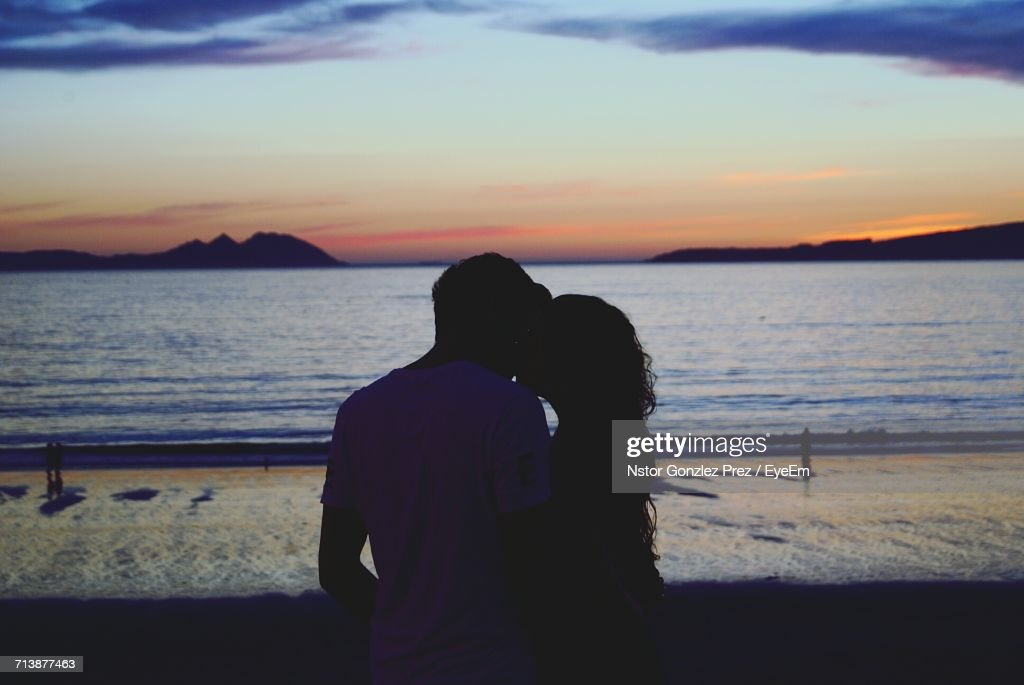 Silhouette Couple Kissing While Standing At Beach During Sunset