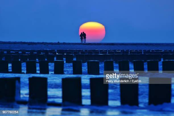 Silhouette Couple On Pier By Sea Against Clear Sky During Sunset