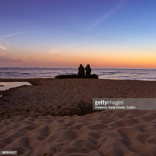 Silhouette Couple Sitting At Beach Against Clear Sky During Sunset