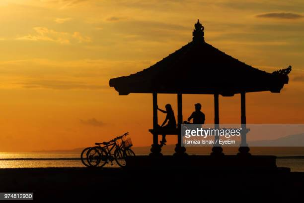 Silhouette Couple Sitting By Sea In Gazebo During Sunset