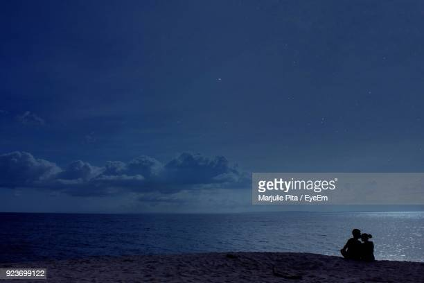 Silhouette Couple Sitting On Beach Against Sky At Night