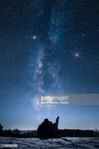 silhouette couple sitting on mountain against star field at night - astronomy stock pictures, royalty-free photos & images