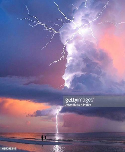 Silhouette Couple Standing At Beach Against Forked Lightning In Sky At Sunset