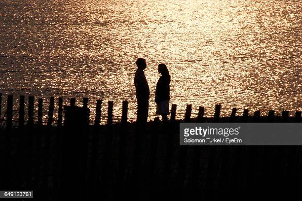 silhouette couple standing at beach during sunset - solomon turkel stock pictures, royalty-free photos & images