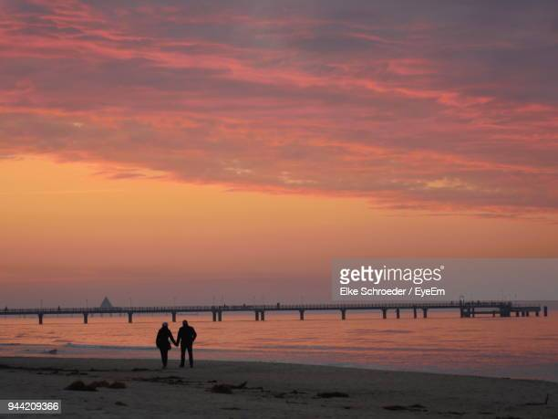 silhouette couple standing at beach during sunset - ウセドム ストックフォトと画像