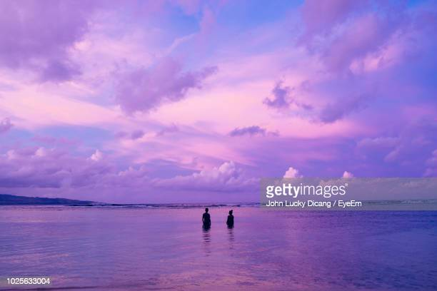 silhouette couple standing in sea against purple sky during sunset - 紫 ストックフォトと画像