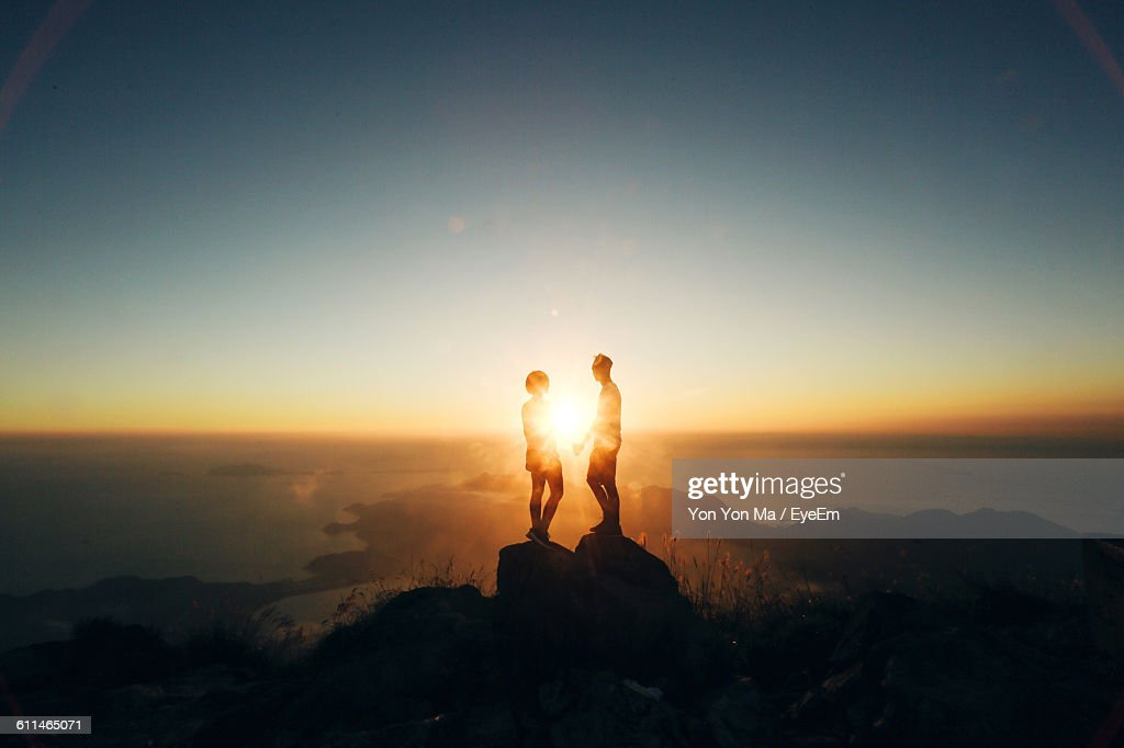 Silhouette Couple Standing On Rock Formation Against Sky During Sunset : Stock-Foto