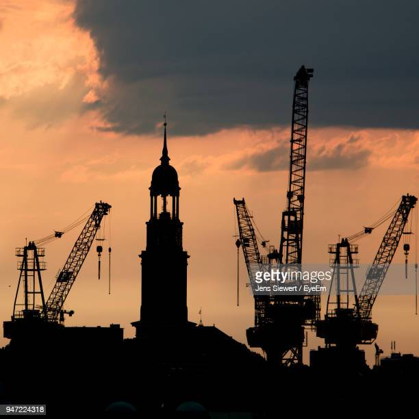 Silhouette Cranes Against Sky During Sunset