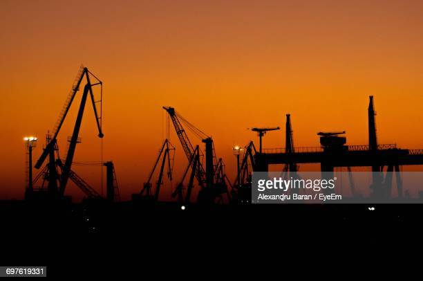 Silhouette Cranes At Against Clear Orange Sky During Sunset