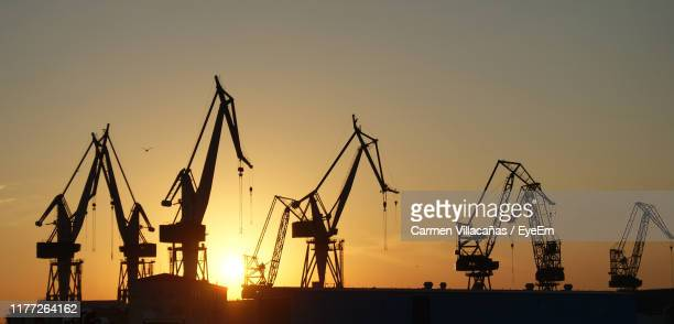 silhouette cranes at commercial dock against sky during sunset - イストリア半島 プーラ ストックフォトと画像