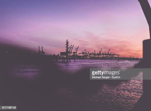 Silhouette Cranes In Front Of River Against Sky At Harbor