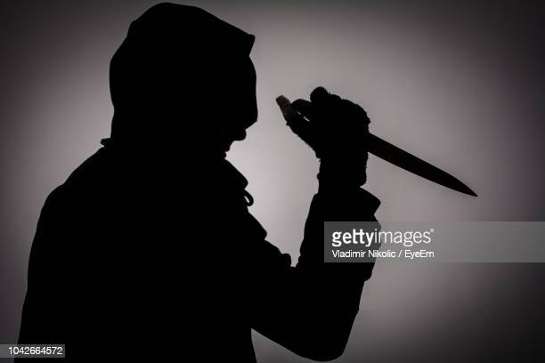 silhouette criminal holding knife against gray background - murder stock pictures, royalty-free photos & images