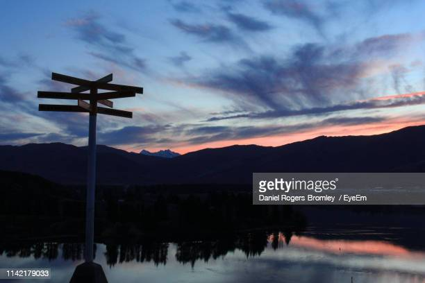 silhouette cross on lake against sky during sunset - faith rogers stock pictures, royalty-free photos & images