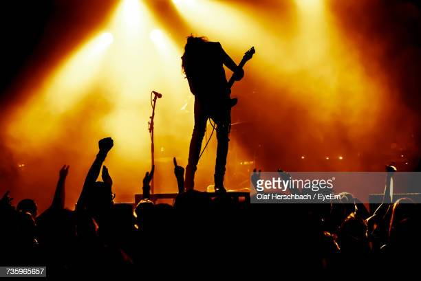 Silhouette Crowd Enjoying While Guitarist Playing Guitar On Stage During Concert