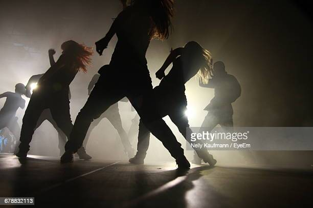 silhouette dancers performing on stage - パフォーマンス ストックフォトと画像