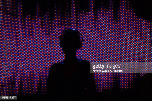 silhouette dj playing music at night club - dj photos et images de collection