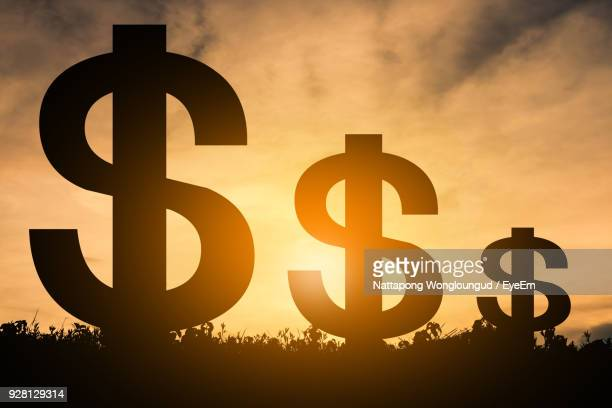 silhouette dollar sign against sky during sunset - dollar sign stock pictures, royalty-free photos & images