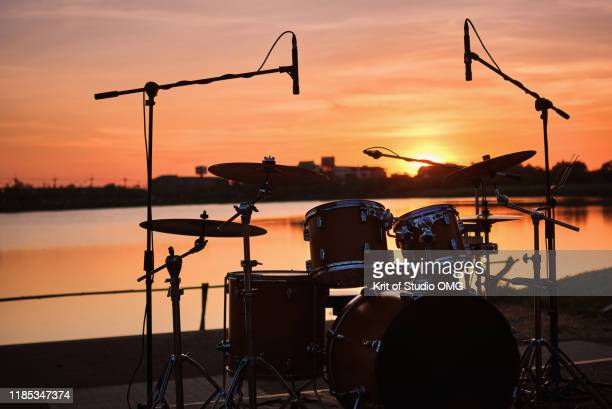 silhouette drum kit by the lake - tranquil scene photos et images de collection