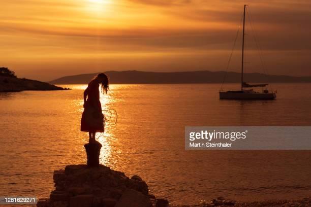 silhouette einer frau in rotem sommer - kleid steht felsen im sonnenuntergang - kleid stock pictures, royalty-free photos & images