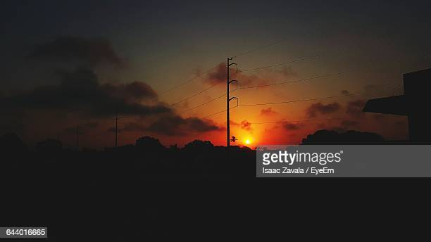 silhouette electric pole on field against orange sky - タマウリパス州 ストックフォトと画像