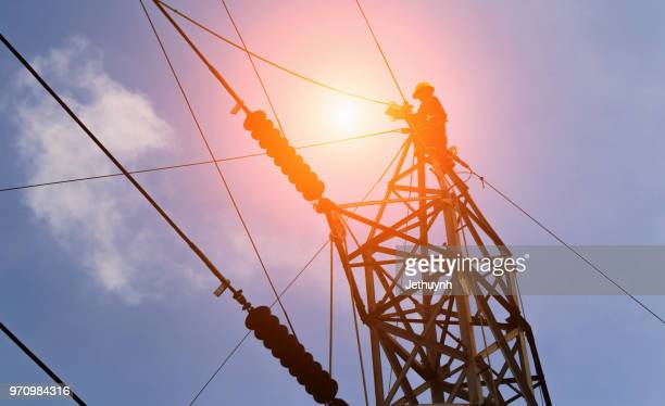 silhouette electrician workers on electricity pylon against sky - power occupation stock photos and pictures