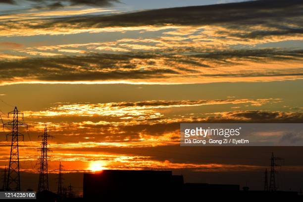 silhouette electricity pylon against dramatic sky during sunset - 富山県 ストックフォトと画像