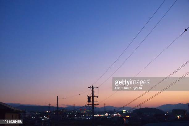 silhouette electricity pylons against clear sky at sunset - 夕暮れ ストックフォトと画像