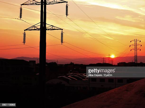 Silhouette Electricity Pylons Against Orange Sunset Sky