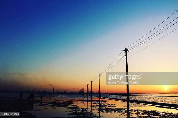 Silhouette Electricity Pylons On Shore Against Clear Sky During Sunset