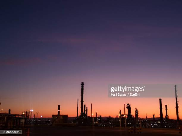 silhouette factory against sky during sunset - middle east stock pictures, royalty-free photos & images