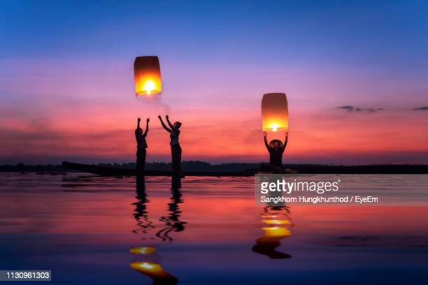 silhouette family releasing illuminated lanterns while standing in sea at dusk - releasing stock photos and pictures