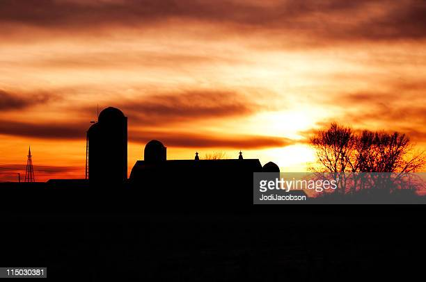 Silhouette de ferme au coucher du soleil