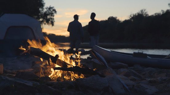 Silhouette father and son standing at lakeshore with campfire burning in foreground - gettyimageskorea