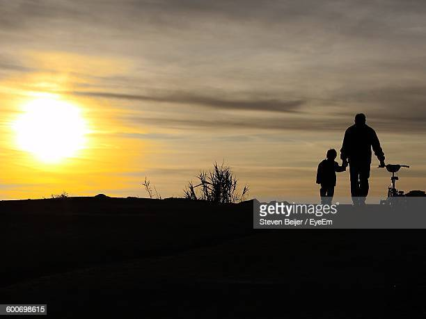 Silhouette Father And Son Walking With Bicycle On Field Against Sunset Sky