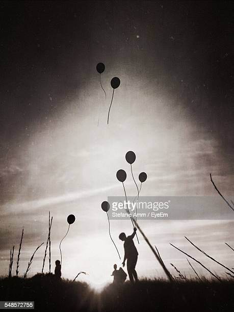 Silhouette Father With Children Releasing Balloons In Sky