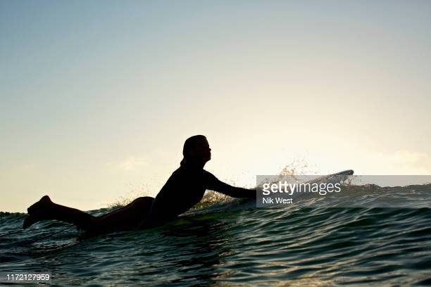 silhouette female surfer paddling out - paddling stock pictures, royalty-free photos & images