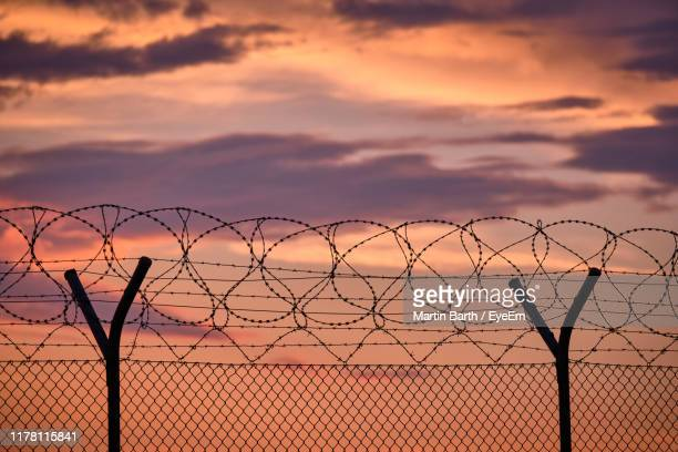 silhouette fence against sky during sunset - barbed wire stock pictures, royalty-free photos & images