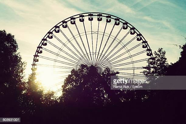 Silhouette Ferris wheel against clouds
