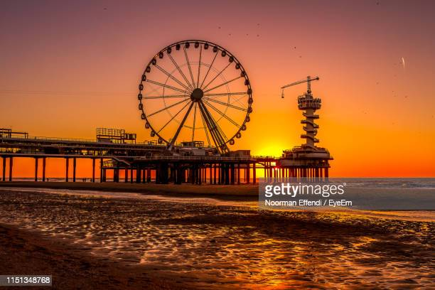silhouette ferris wheel and built structure by sea against sky during sunset - scheveningen stock pictures, royalty-free photos & images