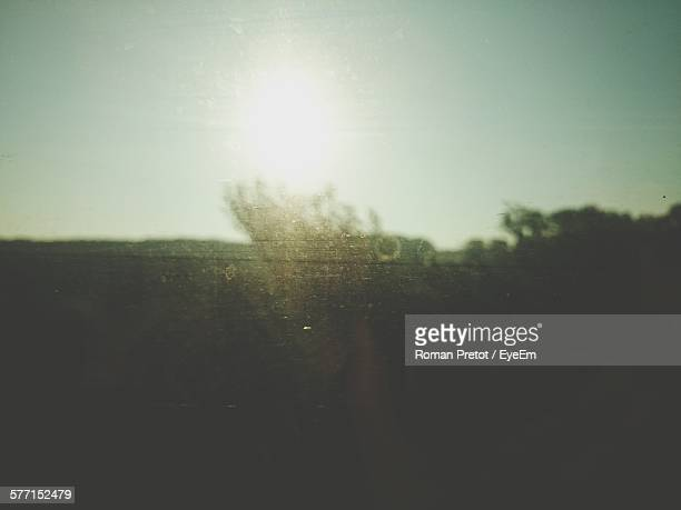 silhouette field against sky seen through glass window - roman pretot stock-fotos und bilder