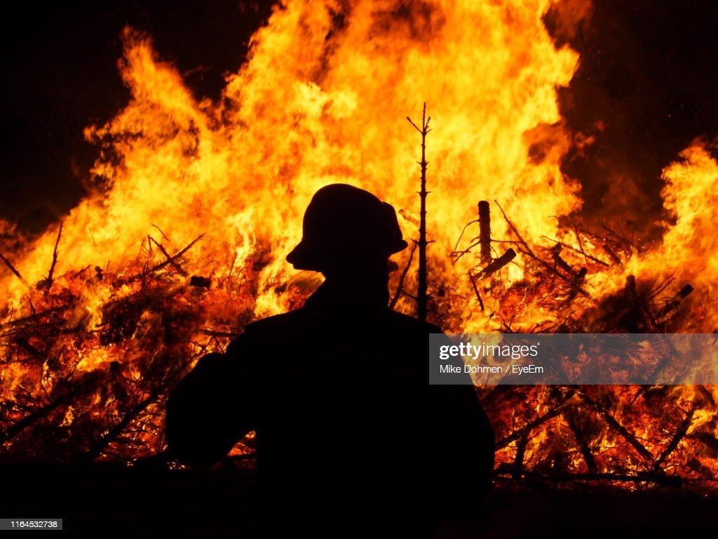 Silhouette Firefighter Standing By Bonfire At Night : Stock Photo