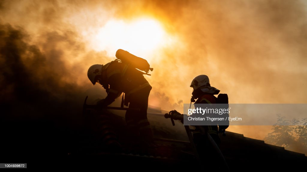 Silhouette Firefighters Against Sky During Sunset : Stock Photo
