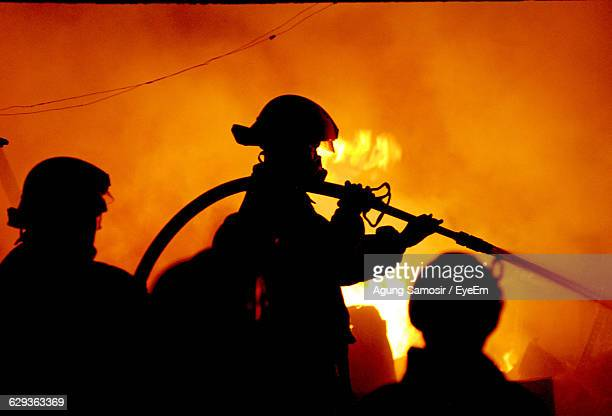 Silhouette Firefighters Extinguishing Fire