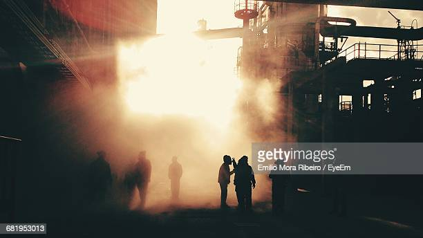 silhouette firefighters in factory at sunset - accidents and disasters photos stock photos and pictures
