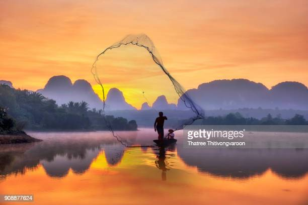 silhouette fisherman a silhouette fisherman throw a net to catch a fish in a river with morning sun. - phuket province stock pictures, royalty-free photos & images