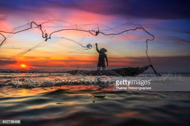 Silhouette Fisherman of traditional fishermen throwing net fishing at sunrise time