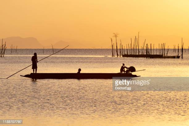 silhouette fisherman punting boat after fishing at sunset, songkhla lake, songkhla province, thailand - provincia di songkhla foto e immagini stock