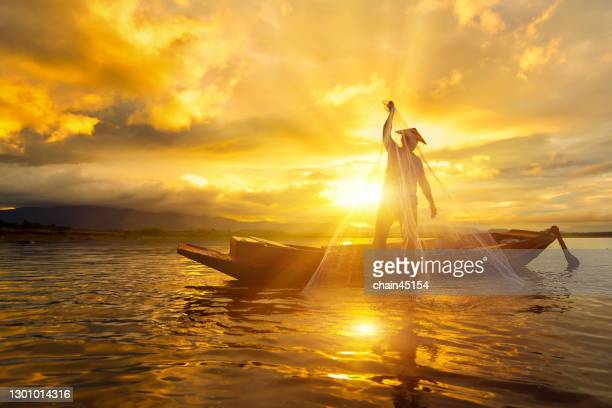 silhouette fisherman use fishing nets for fishing on the boat. - thai ethnicity stock pictures, royalty-free photos & images