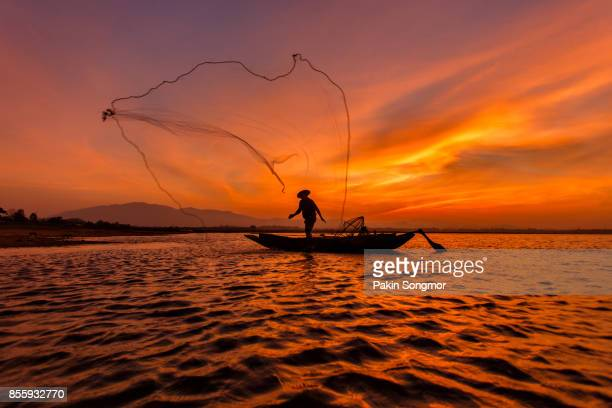 silhouette fisherman with net at the lake in thailand - 網状 ストックフォトと画像