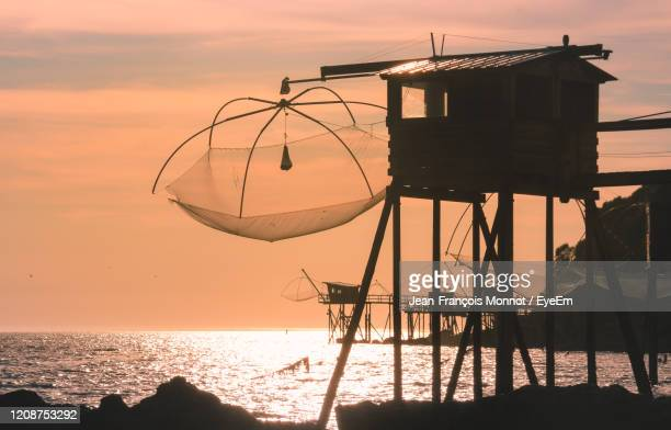 silhouette fishing huts by sea against sky during sunset - loire atlantique stock pictures, royalty-free photos & images